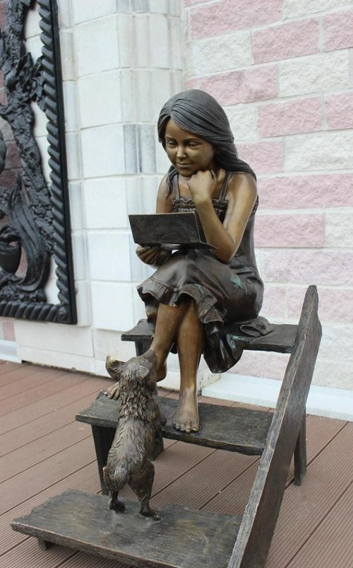 Park sculpture of girl with a dog